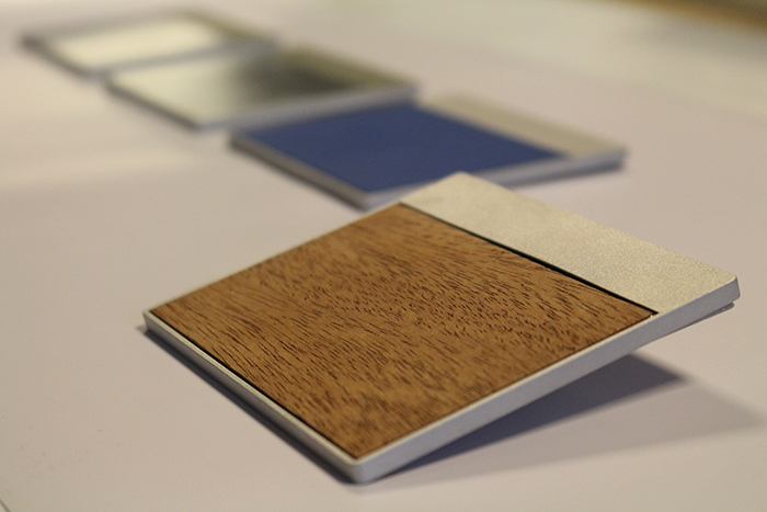 Embed haptic features in materials such as glass, wood, plastic, and metal.